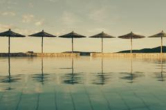 Stock Photo of Croatia, Sibenik, Sunshades, Swimming pool of a hotel facility, Evening mood