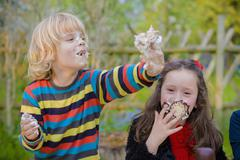 Stock Photo of Three children making eating contest with chocolate marshmallows