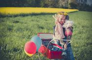 Stock Photo of Smiling little girl holding doll and soft toy standing on meadow with doll