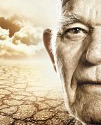 elderly man's face over dry desert land background - stock illustration