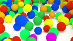 Falling colored spheres. - stock footage