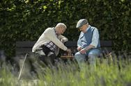 Stock Photo of Two old friends sitting on park bench playing chess