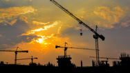 Stock Video Footage of time lapse sunset and silhouette crane working in construction site (zoom in)