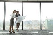 Stock Photo of Two businesswomen in office looking at blueprint