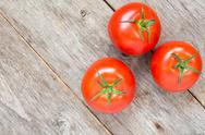 Stock Photo of three tomatoes on wooden background