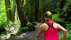 Couple jogging together in the forest, slow motion shto at 240fps Stock Footage