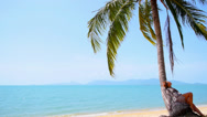 Stock Video Footage of Young Woman Sitting on the Sunny Beach on Palm Tree.