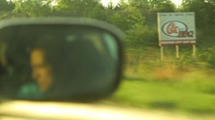 Face in rearview side car mirror driving highway billboard barn sunrise sunset Stock Footage
