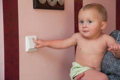 interested little boy turning off the light-switch - stock photo