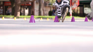 Stock Video Footage of Male and female weave between row of cones with skates and scooters
