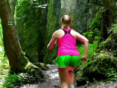 Woman jogging in the green forest, steadycam shot, slow motion shot at 240fps Stock Footage