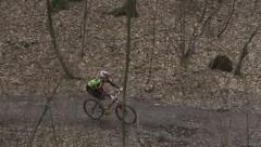 Woman riding on bike down on hill, steadycam shot Stock Footage
