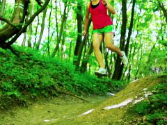 Woman jumping from hill in forest, steadycam shot, slow motion shot at 240fps Stock Footage