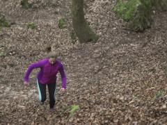 Woman running up on hill, steadycam shot, slow motion shot at 240fps Stock Footage