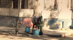 An old man pumps water in Calcutta, India. Stock Footage