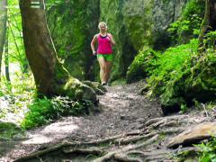 Woman jogging in forest, steadycam shot, slow motion shot at 240fps Stock Footage