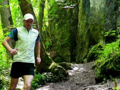 Man running in forest, steadycam shot, slow motion shot at 240fps Stock Footage