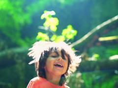 Happy kid jumping in forest, steadycam shot, slow motion shot at 240fps Stock Footage