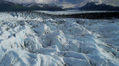 Aerial view Knik Glacier moraine crevasses feeding the Knik River, Alaska, USA Stock Footage