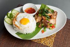 Traditional thai dish crispy pork with a fried egg atop the jasmine rice serv Stock Photos