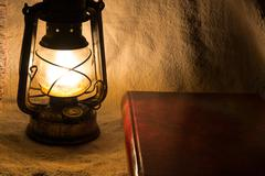 set with an old rusty lantern and a book - stock photo