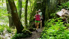 Couple jogging in the forest, steadycam shot, slow motion shot at 240fps Stock Footage