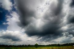 Agressive thunderstorm cloouds sky over farm land Stock Photos