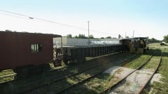 Diesel locomotive moving past parked carriages 4K - stock footage