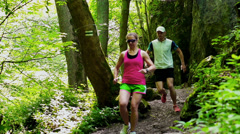 Couple running together in forest, steadycam shot, slow motion shot at 240fps Stock Footage