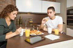 Serious and bored couple having a home breakfast Stock Photos