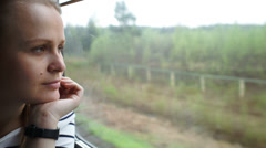 Young woman looking out the window of moving train Stock Footage