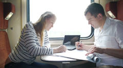 Man and woman discussing drawing during business trip in the train Stock Footage