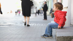 Little boy sitting alone in the street, people passing by Stock Footage