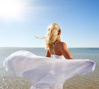 Blond woman with white shawl relaxing near the sea Stock Illustration
