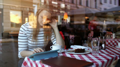 Woman in cafe using tablet PC and eating dessert Stock Footage