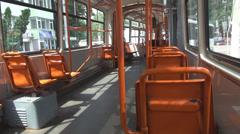 Steady shot inside stopped tram summer day, empty orange sits, few people travel Stock Footage