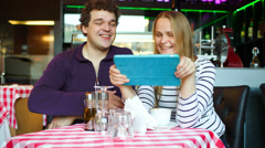 Young couple in cafe having a video chat on tablet PC Stock Footage