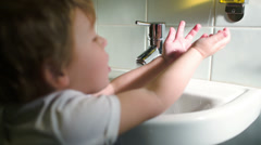 Boy washing hands with soft soap and turning off water Stock Footage