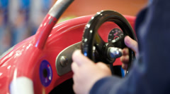 Child turning steering wheel of a toy car Stock Footage