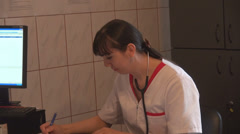 Very busy medical assistant nurse writing hurry medical prescriptions to patient - stock footage
