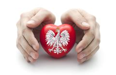 Hands covering Polish coat of arms on a red heart - stock photo