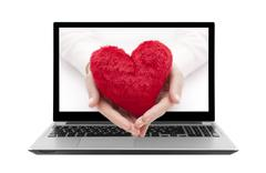 Laptop with red heart in woman hands. Clipping path included. Stock Illustration