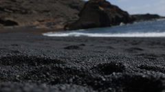 Black Sand with beach in background Stock Footage