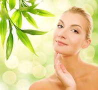 beautiful young woman applying organic cosmetics to her skin - stock illustration
