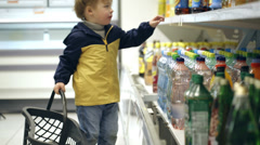 Little boy in the shop putting mineral water into the basket Stock Footage