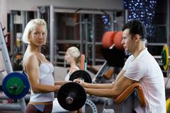 Handsome young man lifting weights assisted by a female trainer Stock Photos