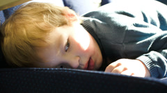 Little boy lying on the seat in the bus, car ot train Stock Footage