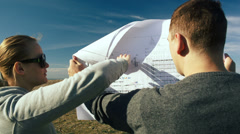 Young architects examining open territory using their plans Stock Footage
