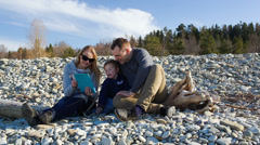 Family of three sitting on the stony shore and watching something on pad Stock Footage