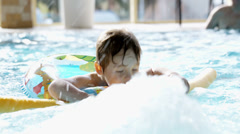 Little boy swimming in the pool with rubber ring Stock Footage
